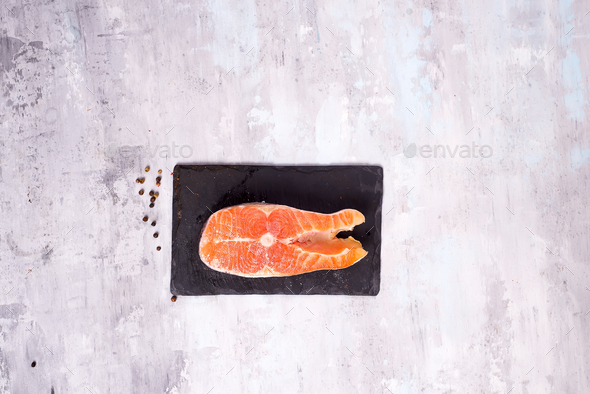 Raw salmon filet on dark slate cutting board. Lean proteins. - Stock Photo - Images