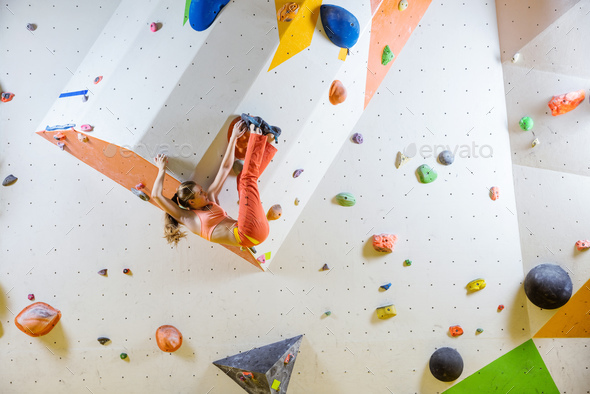 Young woman bouldering challenging route in climbing gym - Stock Photo - Images
