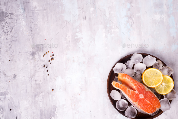 Salmon steaks on ice with lemon slice on wooden plate - Stock Photo - Images