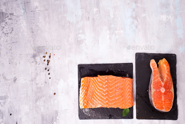 two fresh raw salmon steaks are laying on the dark slate board. - Stock Photo - Images