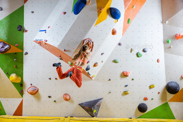 Young athletic woman jumping on climbing hold in bouldering gym - Stock Photo - Images