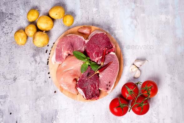 Selection of different raw meat with vegetables at wooden board .Lean proteins. - Stock Photo - Images
