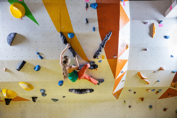 Young woman bouldering in climbing gym - Stock Photo - Images