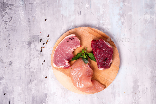 Fresh raw meat - beef, pork and chicken on a wooden background. Lean proteins. - Stock Photo - Images