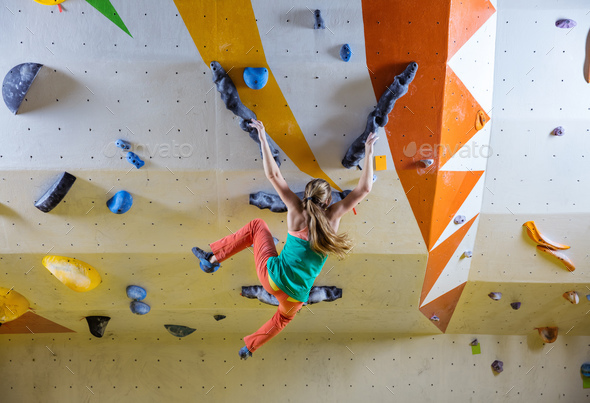 Young woman falling down while bouldering in climbing gym - Stock Photo - Images