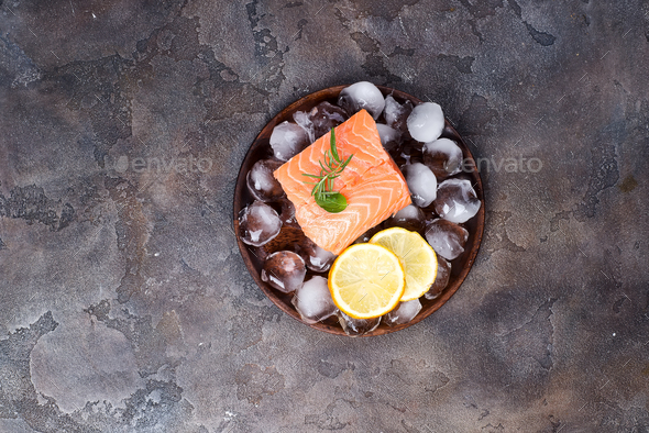 Salmon steaks on ice with lemon slice on wooden plate. Lean proteins. - Stock Photo - Images