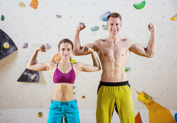 Young cheerful female and male rock climbers flexing biceps - Stock Photo - Images