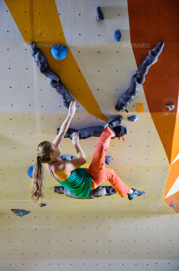 Young woman climbing bouldering route - Stock Photo - Images