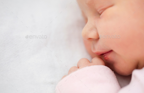 Closeup ofe beautiful one day old girl smiling in her sleep - Stock Photo - Images