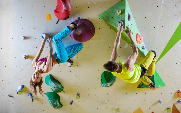 Rock climbers in bouldering gym climbing up overhanging wall - Stock Photo - Images