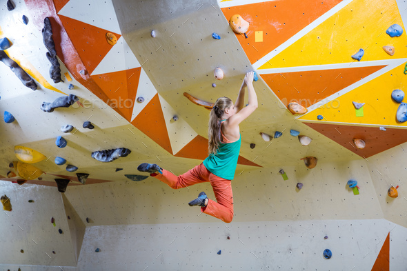 Young woman jumping on handhold in bouldering gym - Stock Photo - Images