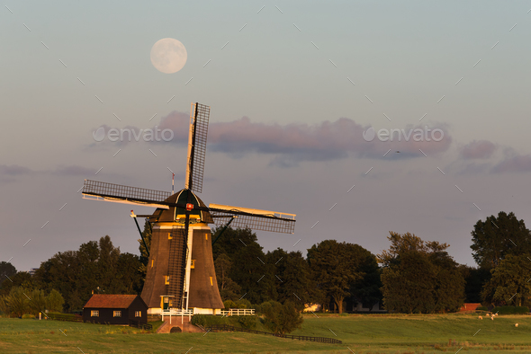 Full moon over a traditional windmill - Stock Photo - Images