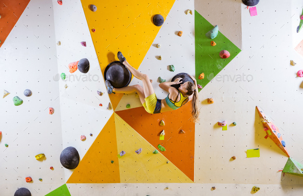 Young woman bouldering in indoor climbing gym - Stock Photo - Images