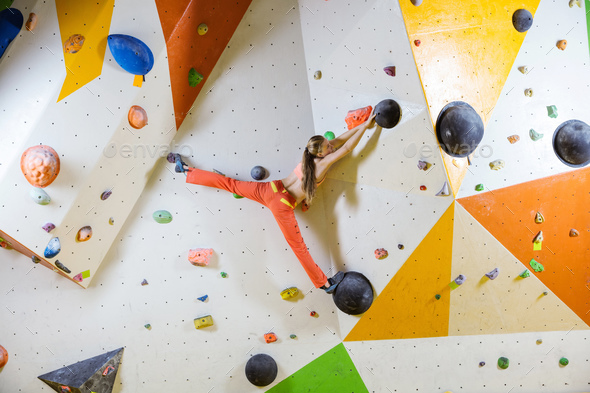 Young woman climbing challenging bouldering route - Stock Photo - Images
