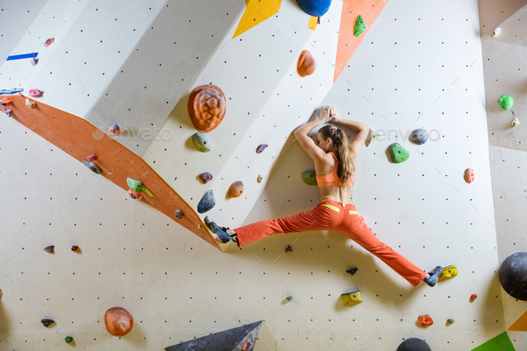 Young woman climbing challenging bouldering route. In climbing gym. - Stock Photo - Images
