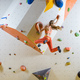 Young woman jumping on handhold in bouldering gym - PhotoDune Item for Sale