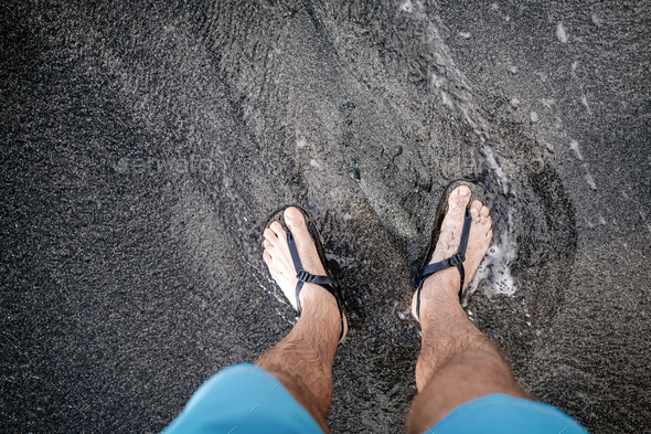 Man looking down at feet and sandals on volcanic black sand beac - Stock Photo - Images