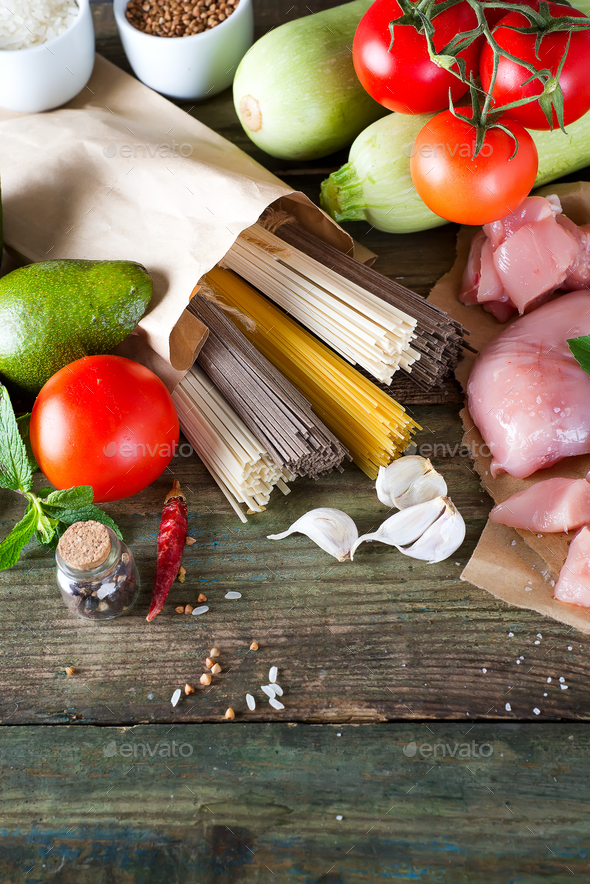 bunch of Italian spaghetti, noodles soba and sommel, chicken raw meat, avocado, zucchini with tomato - Stock Photo - Images