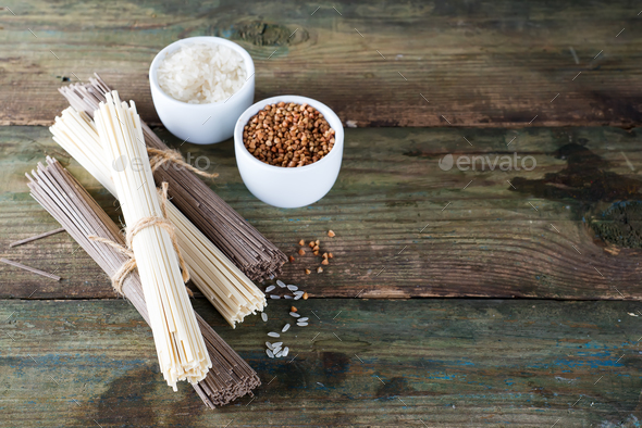 noodles soba and sommel, bowls with buckwheat and rice on an old wooden background - Stock Photo - Images