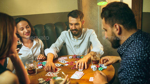 Side view photo of friends sitting at wooden table. Friends having fun while playing board game. - Stock Photo - Images