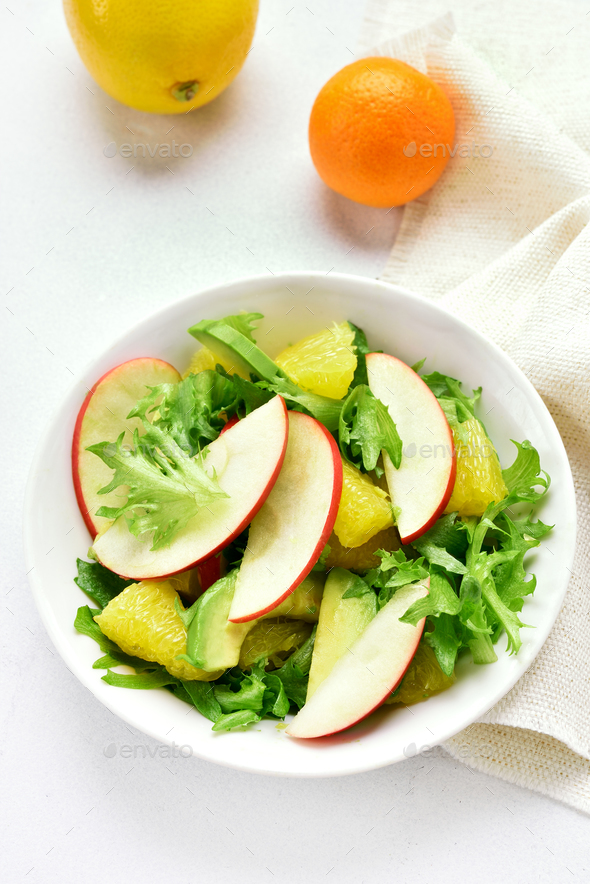 Fruit vegetable salad with red apples, avocado, orange slices - Stock Photo - Images