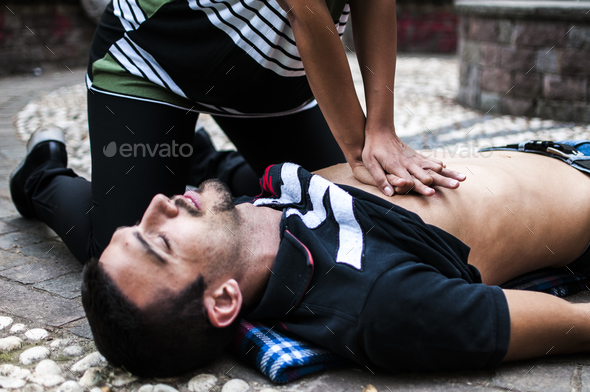 cardiac massage to an unconscious guy after injury - Stock Photo - Images
