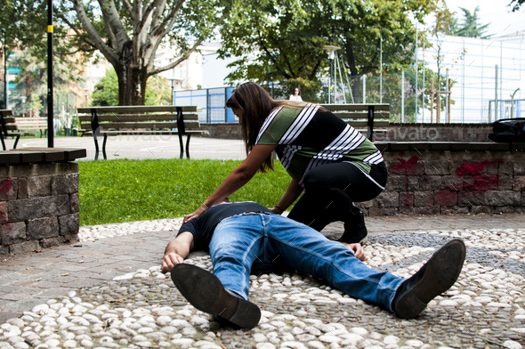 girl trying to find help for an unconscious guy - Stock Photo - Images