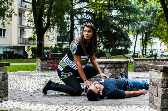 girl assists an unconscious guy after accident - Stock Photo - Images