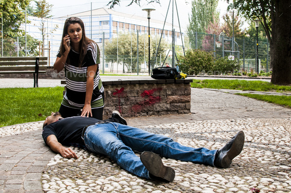 girl calling emergency service to assist a guy with cpr - Stock Photo - Images