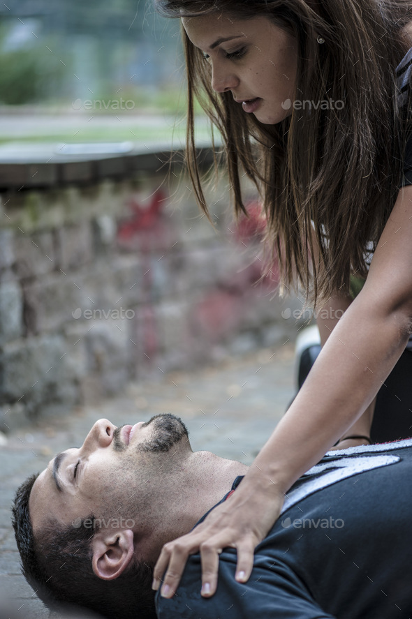 girl helping an unconscious guy with cpr and cardiac massage - Stock Photo - Images