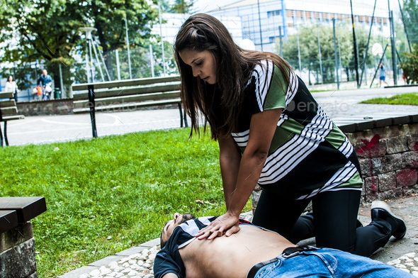 girl making cardiopulmonary resuscitation to an unconscious guy after heart attack - Stock Photo - Images