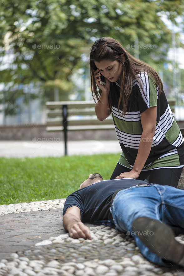 girl calling emergency service for an unconscious guy - Stock Photo - Images