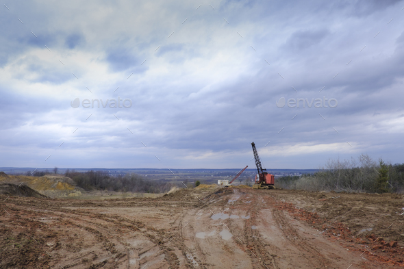 Excavators in the red clay quarry - Stock Photo - Images