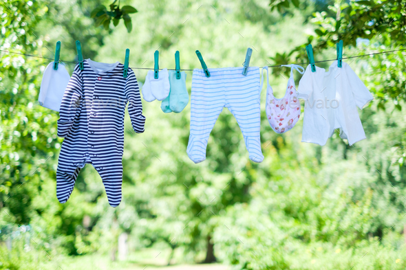 Baby clothes on clothesline in garden - Stock Photo - Images