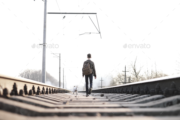 Teenager on railway walking with small white dog - Stock Photo - Images