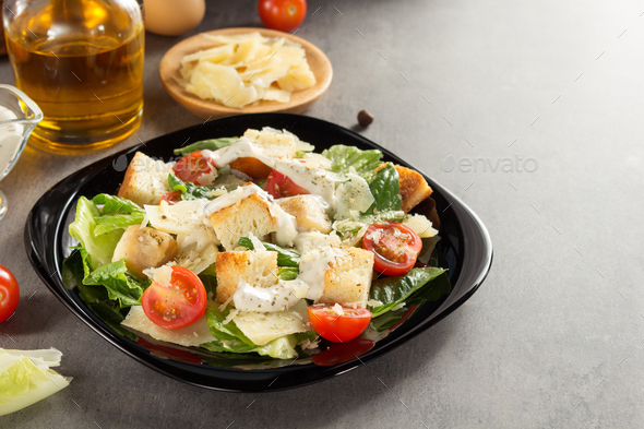 caesar salad and ingredients at table - Stock Photo - Images