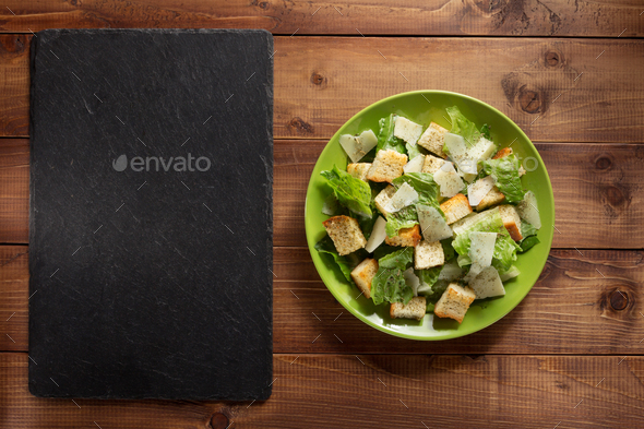 caesar salad in plate at wood - Stock Photo - Images