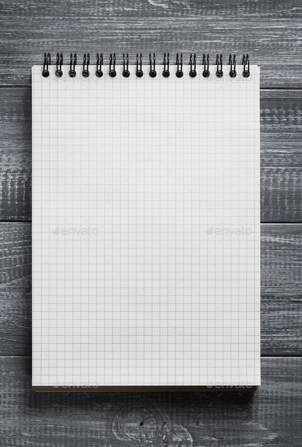 checked notebook on wooden table - Stock Photo - Images