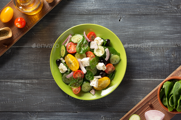 fresh greek salad in plate and ingredients - Stock Photo - Images
