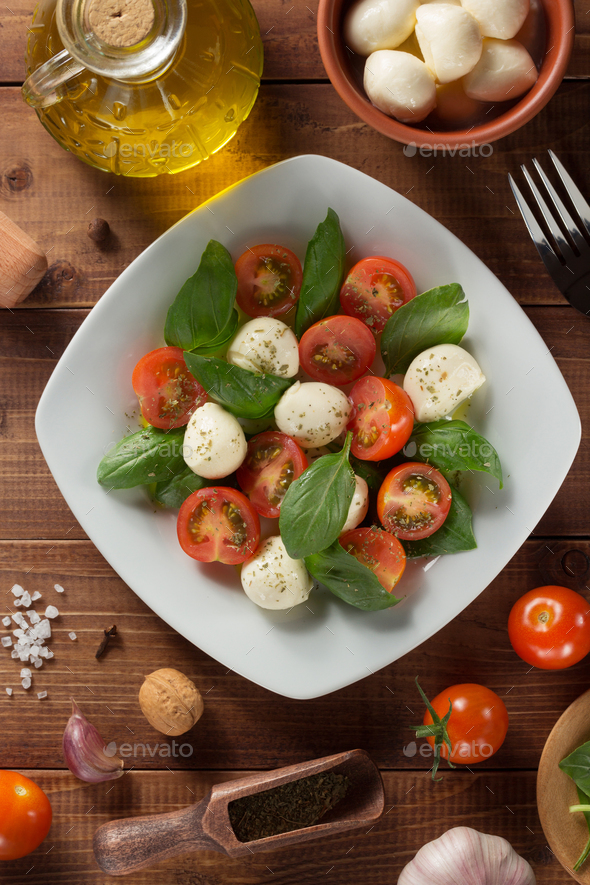 caprese salad and ingredients at wood - Stock Photo - Images