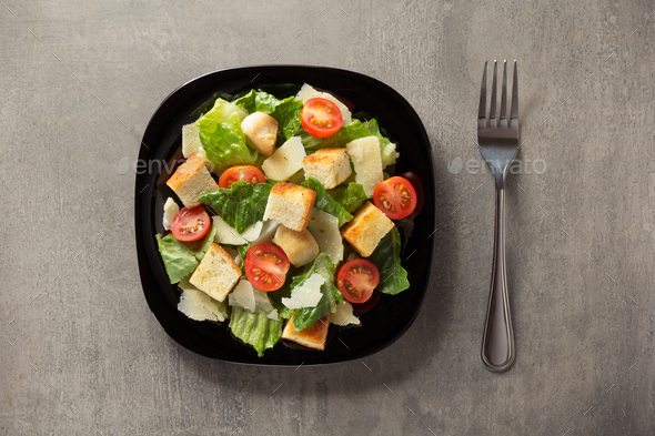caesar salad in plate at table - Stock Photo - Images