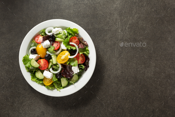 fresh greek salad in plate on stone - Stock Photo - Images