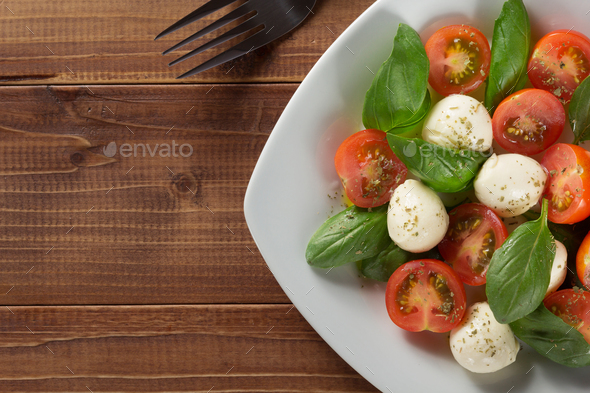 caprese salad in plate at wood - Stock Photo - Images