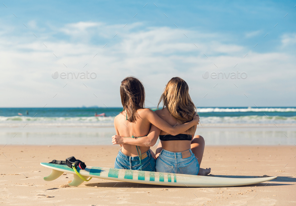 Two surfer girls at the beach - Stock Photo - Images