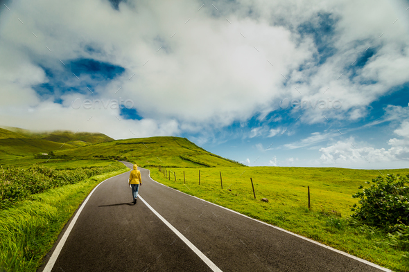 Woman walking over a beautiful road - Stock Photo - Images