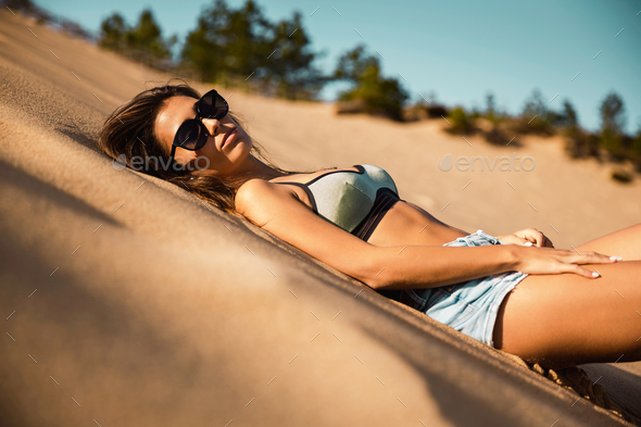 Young girl lying on a sand dune - Stock Photo - Images