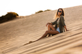 Young girl sitting on a sand dune - PhotoDune Item for Sale
