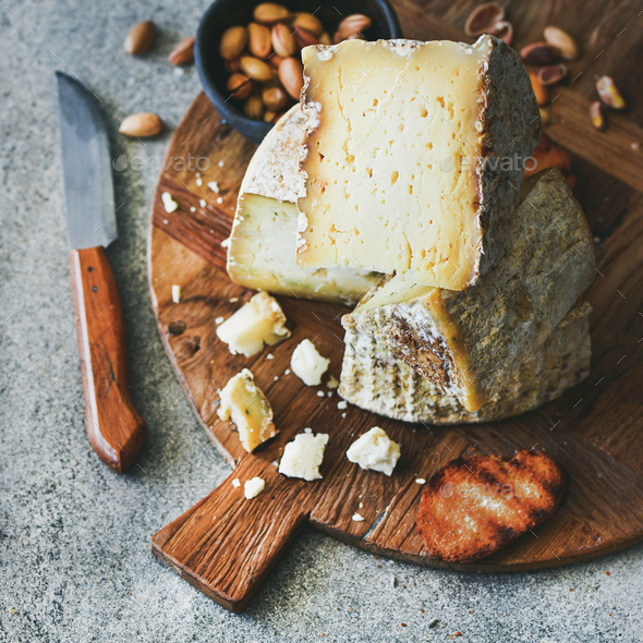 Cheese platter with nuts, honey and bread, square crop - Stock Photo - Images
