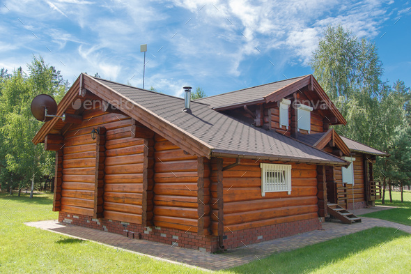 A modern wooden house made of logs. View from outside in summer - Stock Photo - Images