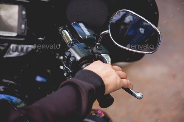 Close up Hand a man hold manual brake and stop running of motor cycle safety concept on the road - Stock Photo - Images